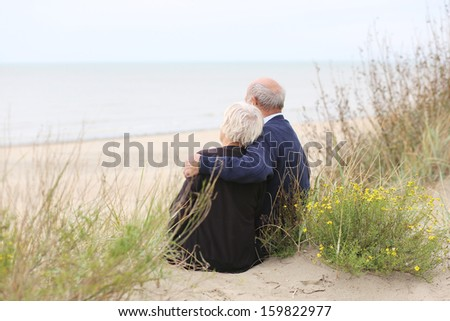 Back view of senior loving couple, a man with his wife sitting together on sandy peaceful beach relaxing and looking at the ocean - stock photo