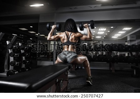 back view of sexy fitness girl  in sport wear with perfect fitness body in gym performing shoulder exercises with dumbbell - stock photo
