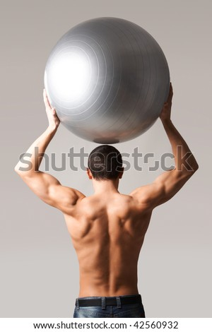 Back view of shirtless man in jeans holding big ball above head - stock photo