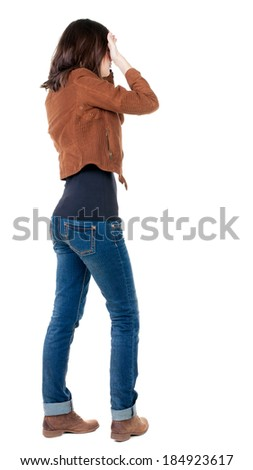 Back view of shocked woman in blue jeans. girl hid his eyes behind his hands.  Rear view people collection.  backside view of person.  Isolated over white background. - stock photo
