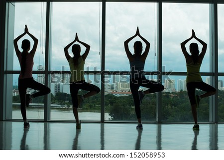 Back view of sportswomen standing in yoga position  - stock photo