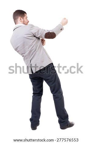 back view of standing man pulling a rope from the top or cling to something.  Rear view people collection.  backside view of person.  Businessman pulling a rope something from the top right. - stock photo