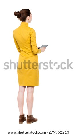 back view of standing young beautiful  girl with tablet computer in the hands of. girl  watching. Rear view people collection.  Girl in mustard strict dress holding plate and looks ahead. - stock photo