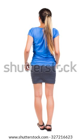 back view of standing young beautiful  woman.  girl  watching. Rear view people collection.  backside view of person.  Isolated over white background. Girl in a gray skirt and blue shirt stands - stock photo
