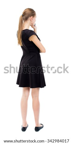 back view of standing young beautiful  woman.  girl  watching. Rear view people collection.  backside view of person.  The blonde in a black dress thoughtfully put a hand to his chin. - stock photo
