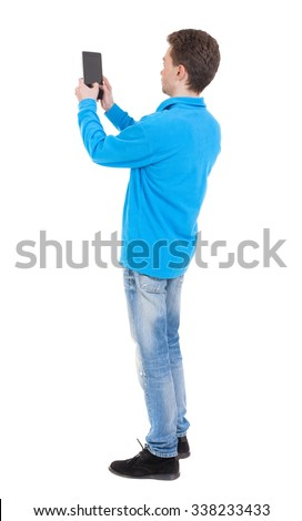 back view of standing young man with tablet computer in the hands of. Rear view people collection.  backside view of person.  Isolated over white background.  - stock photo