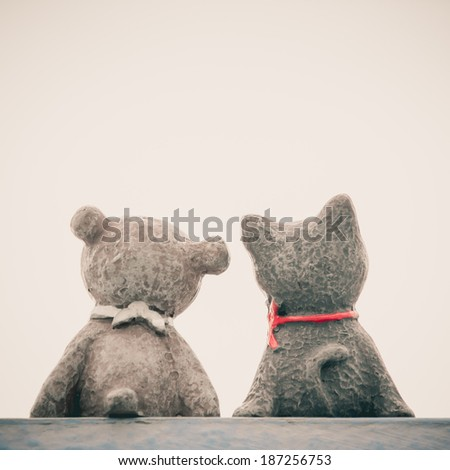 Back view of teddy bear and cat sitting with copy space. Vintage style. Friendship concept. - stock photo