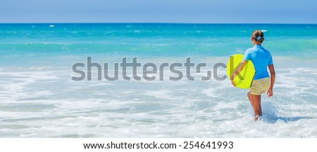 Back view of Teenage girl in blue has fun surfing - stock photo