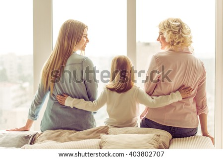 Back view of three generations of beautiful women sitting on sofa against window - stock photo