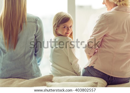 Back view of three generations of beautiful women sitting on sofa against window. Little girl looking at camera and smiling - stock photo