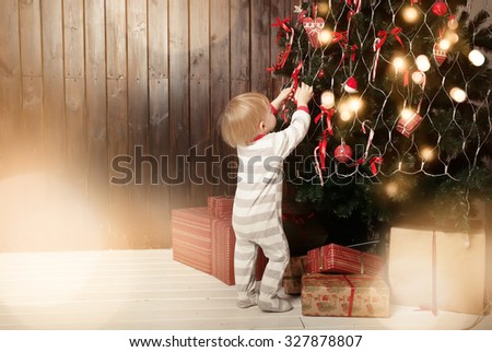 Back view of toddler boy decorating Christmas tree - stock photo