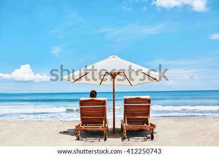 Back View Of Two Deckchairs, Sun Loungers Under Umbrella On Sand Beach. Woman Relaxing On Lounge Chairs Under Tent By Sea. Girl Enjoying Summer Holidays Vacations At Tropical Resort. Summertime Relax - stock photo