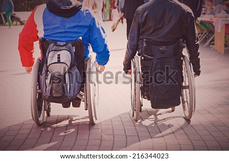 Back view of two men wheelchair during walk in park - stock photo