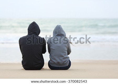 Back view of two sad teenagers sitting on the sand of the beach and looking at horizon in a bad weather day - stock photo