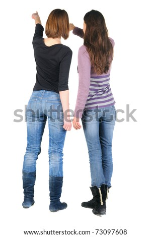 Back view of two women pointing at wall. Rear view. Isolated over white. - stock photo