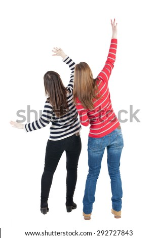 Back view of two young  brunette standing woman  l . beautiful girl friends  discuss. Rear view people collection.  Isolated over white background. Two girls at a concert waving their arms - stock photo