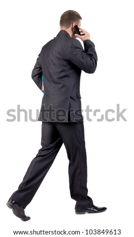 back view of walking  business man with books. going young guy in black suit talking on mobile phone. Isolated over white background. Rear view people collection. backside view of person - stock photo