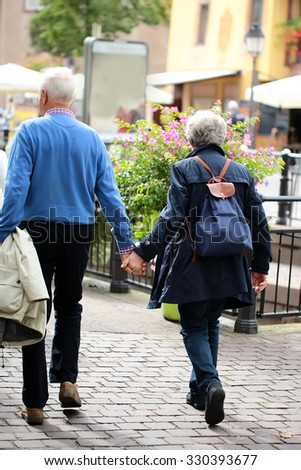 Back view of well-dressed silver-haired senior couple aged man keeping coat and woman wearing rucksack walking down street holding their hands on streetscape background, vertical picture - stock photo