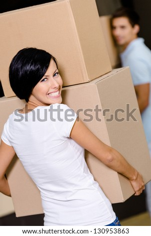 Back view of woman carrying cardboard boxes against the husband while moving to new house - stock photo