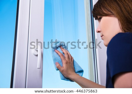 back view of woman cleaning window with special rag - stock photo