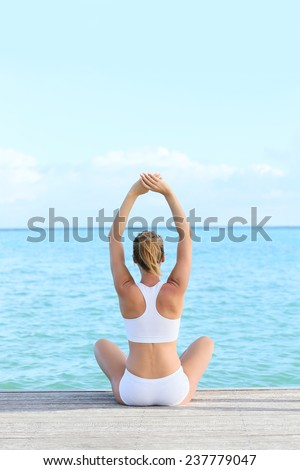 Back view of woman doing yoga exercises on pontoon - stock photo
