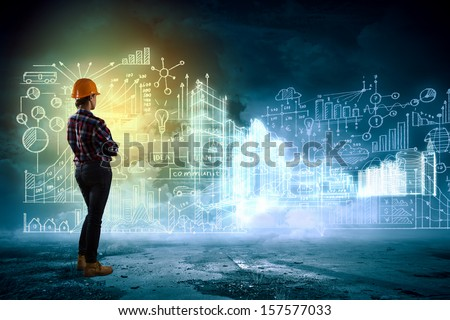 Back view of woman engineer looking at project sketch - stock photo