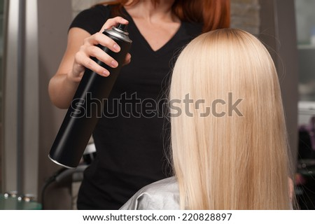 Back view of woman getting new haircut by hairdresser at parlor. redhead hairdresser cutting client's hair in beauty salon - stock photo