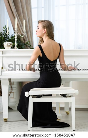 Back view of woman in black dress sitting and playing piano. Concept of music and entertainment - stock photo