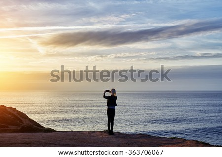 Back view of woman photographing amazing sunset with mobile phone while standing against copy space sea and sky background, hipster girl shoots video of a calm ocean and sunset on mobile phone - stock photo