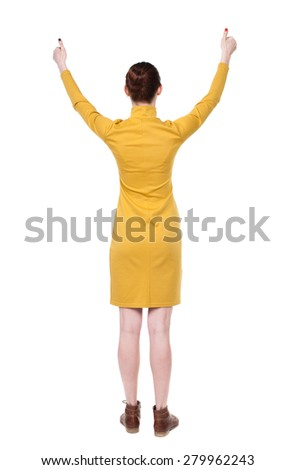 Back view of  woman thumbs up. Rear view people collection. backside view of person. Isolated over white background. Girl in mustard strict dress shows thumb with both hands. - stock photo