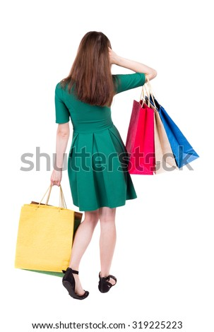 back view of woman with shopping bags . beautiful brunette girl in motion.  backside view of person.  Isolated over white background. Girl in green short dress is looking thoughtfully in front of him. - stock photo