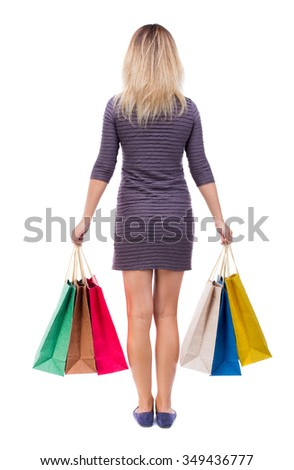 back view of woman with shopping bags . beautiful brunette girl in motion.  backside view of person.  Isolated over white background. Girl in a short dress is holding in both hands paper bags. - stock photo