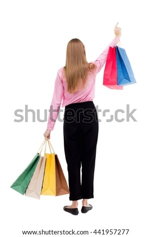 back view of woman with shopping bags . beautiful brunette girl in motion.  backside view of person.  A girl in pink shirt stands with colorful shopping bags and showing thumb up. - stock photo