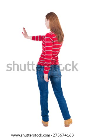 back view of woman. Young woman presses down on something.  backside view of person. she holds his hand open, palm forward. Girl in a striped red sweater showing stopping hand gesture. - stock photo