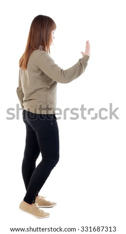 back view of woman. Young woman presses down on something. Isolated over white background. Rear view people collection. backside view of person. she holds his hand open, palm forward.  - stock photo