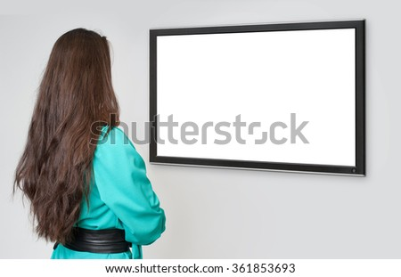 back view of young beautiful woman looking at tv - stock photo