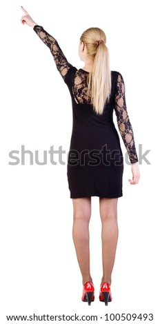 Back view of young blonde woman pointing at wall . beautiful girl in dark dress and red kitten heels showing gesture. Rear view. Isolated over white background.showing gest - stock photo