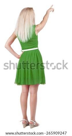 Back view of young blonde woman pointing at wall. beautiful girl in dress. Rear view people collection. backside view of person. Isolated over white background. - stock photo