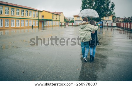 Back view of young couple embracing under the umbrella walking in an autumn rainy day. Love and couple relationships concept. - stock photo