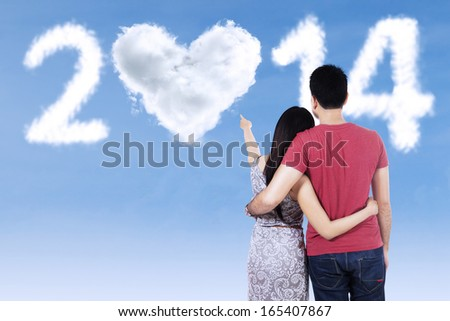 Back view of young couple pointing at clouds shaped 2014 on the sky - stock photo
