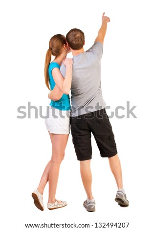 Back view of young couple pointing (woman and man). newlyweds on their honeymoon. . Rear view people collection.   backside view of person.  Isolated over white background. - stock photo
