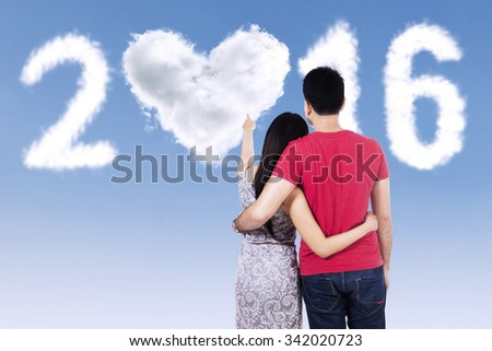 Back view of young couple with casual clothes, looking at clouds shaped numbers 2016 - stock photo