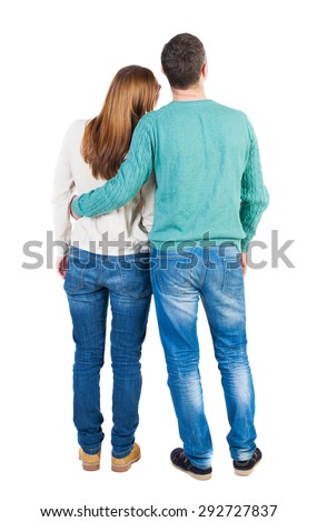 Back view of young embracing couple (man and woman) hug and look into the distance. b  backside view of person.  Isolated over white background. Guy hugs a girl who put her head on his shoulder. - stock photo