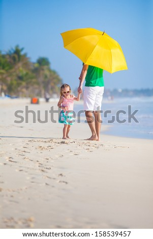 Back view of Young father and his little daughter walking under a yellow umbrella - stock photo