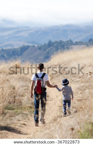 back view of young father and his little son hiking in the park enjoying day together - stock photo