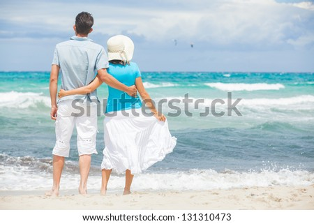 Back view of young man and woman standing on wet sand and looking to sea - stock photo
