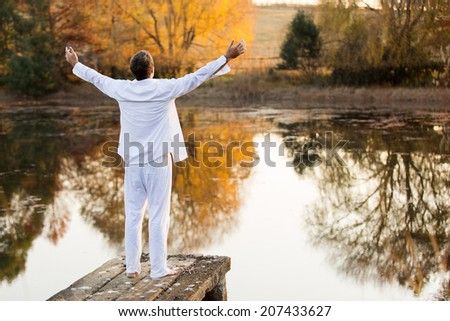 back view of young man standing on pier with arms outstretched - stock photo