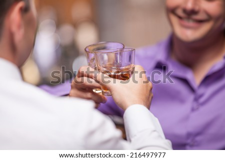 back view of young man talking at counter. closeup of two friends sitting in bar and drinking whisky - stock photo
