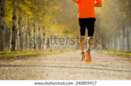 back view of young sport man with strong calves muscle running outdoors in off road trail trees track under beautiful Autumn sunlight in fitness, countryside training and healthy lifestyle concept - stock photo