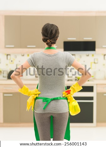 back view of young woman getting ready for kitchen cleaning - stock photo